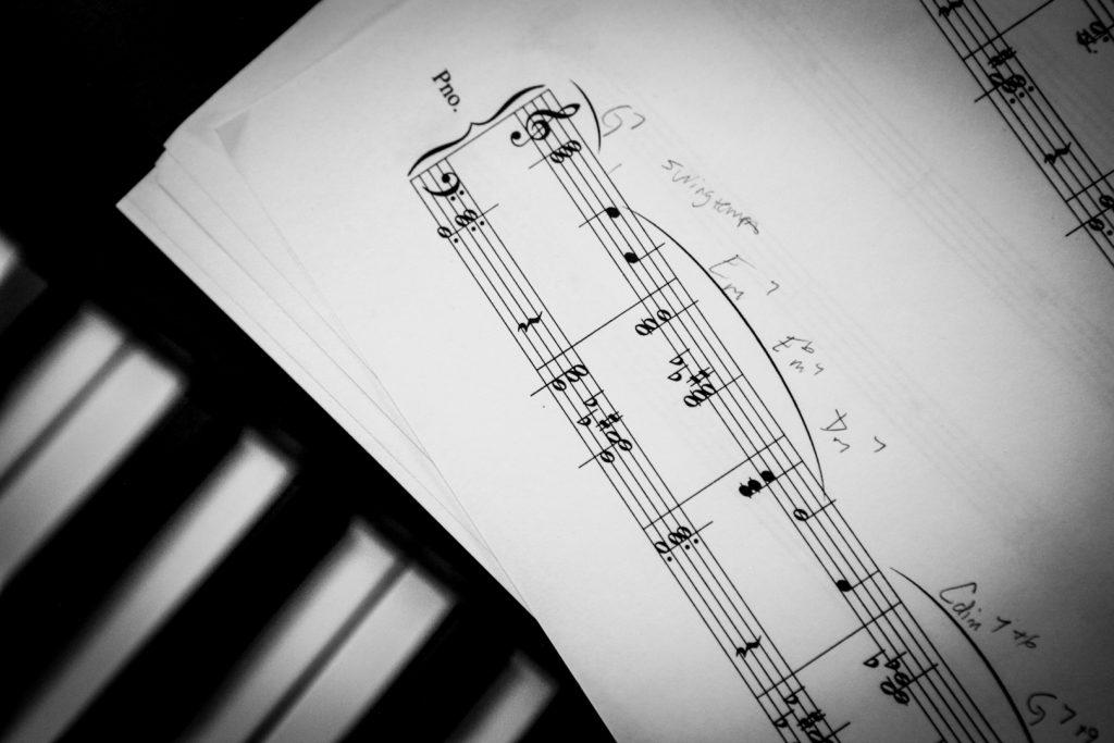 sheet music sits on a piano keyboard